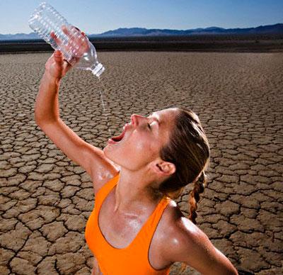 Девушка пьёт воду в пустыне
